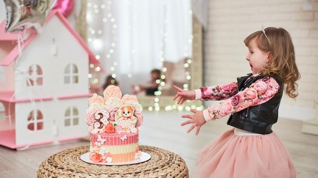 Little girl reaches for birthday cake