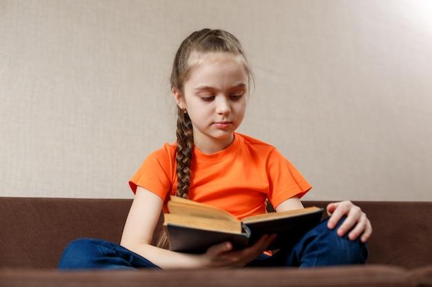 Маленькая девочка читает книгу на диване. кавказский маленькая девочка, проводить время расслабиться на диване со старой книгой.
