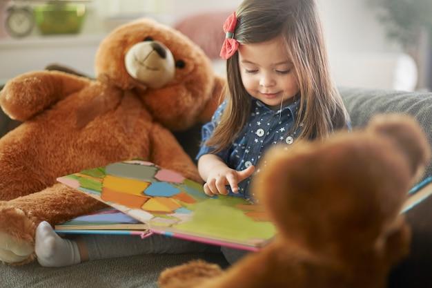 Маленькая девочка читает книгу со своими плюшевыми мишками