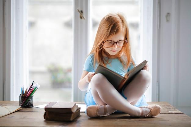 Маленькая девочка читает книгу Premium Фотографии