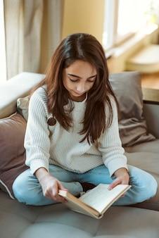 Маленькая девочка читает дома во время карантина