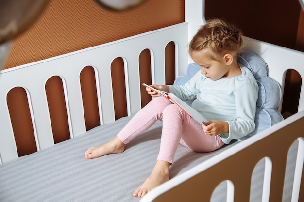 Little girl reading a book in the bedroom.