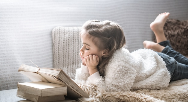 Little girl reading a book on a comfortable sofa, beautiful emotions