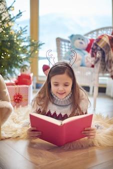 Little girl reading book on the floor
