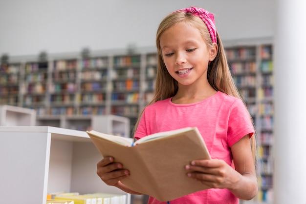 Bambina che legge un libro in biblioteca