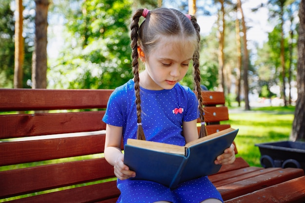Little girl reading a book in the outdoors.