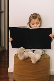 Little girl reading book on pouf