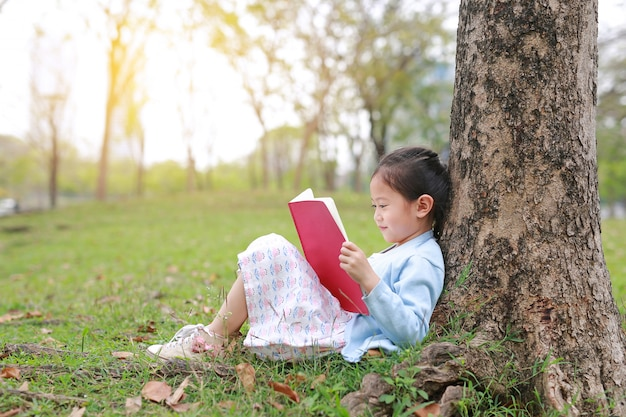 Little girl reading book in summer park outdoor lean against tree trunk in the summer garden.