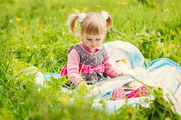 Little girl reading a book in the summer park