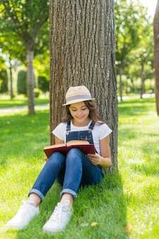 Little girl reading a book next to a tree