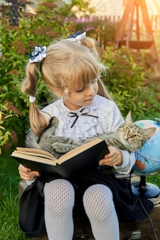 Little girl reading a book with a cat