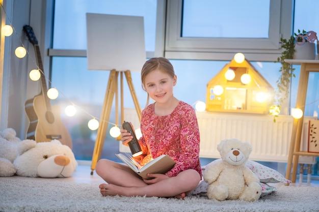 Маленькая девочка, читающая книгу с фонариком в вечерней комнате