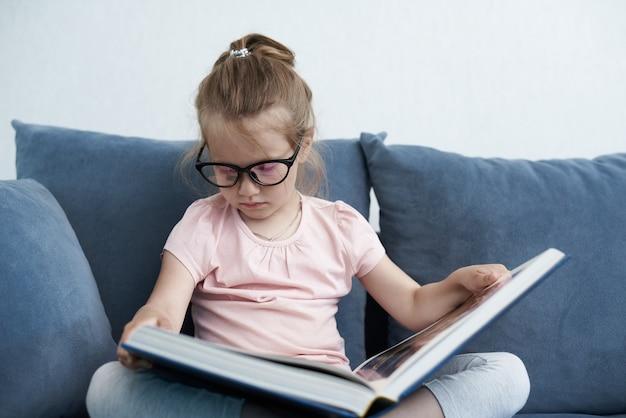 眼鏡をかけて本を読んでいる少女
