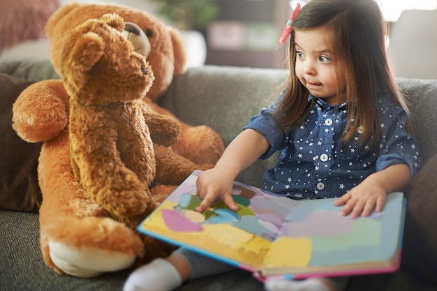 Little girl reading a book with her teddy bears