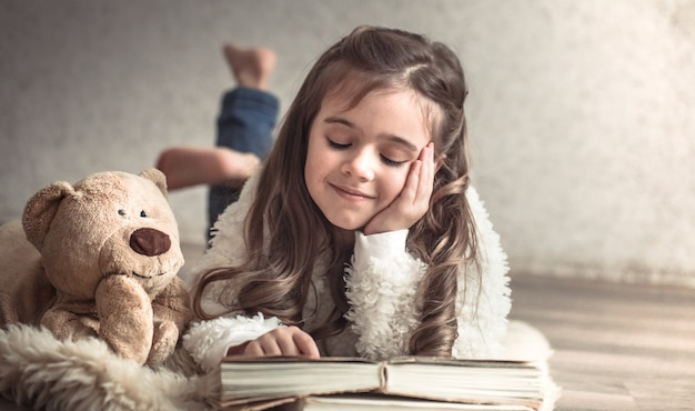 Little girl reading a book with a teddy bear on the floor, concept of relaxation and friendship