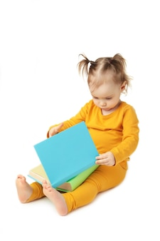 Little girl reading isolated on white. cute baby with book. top view