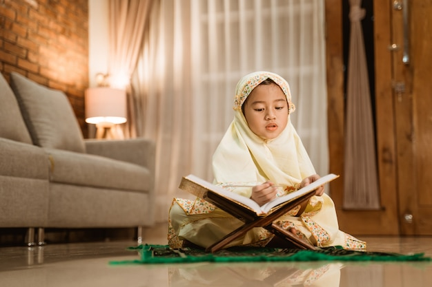 Little girl reading quran wearing muslim hijab