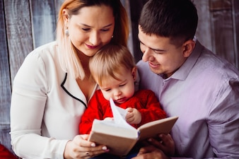 Little girl reads a book sitting with mom and dad