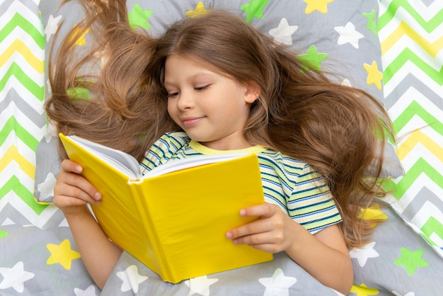 A little girl reads a book with interest in bed before going to bed.