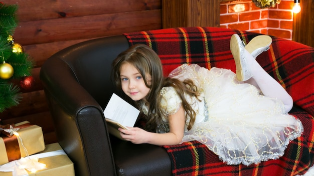 Little girl reads a book with interest.