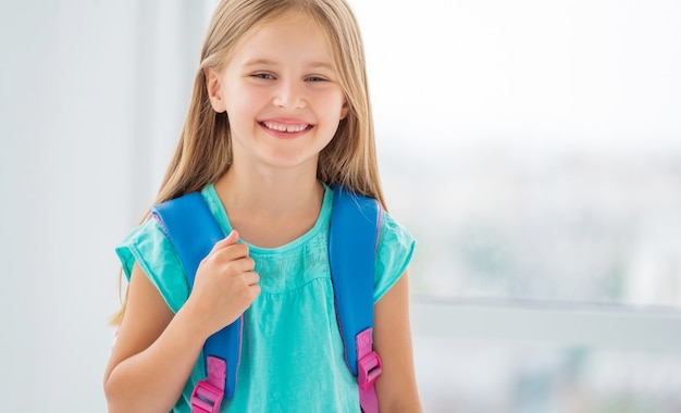 Little girl ready to go to school with backpack