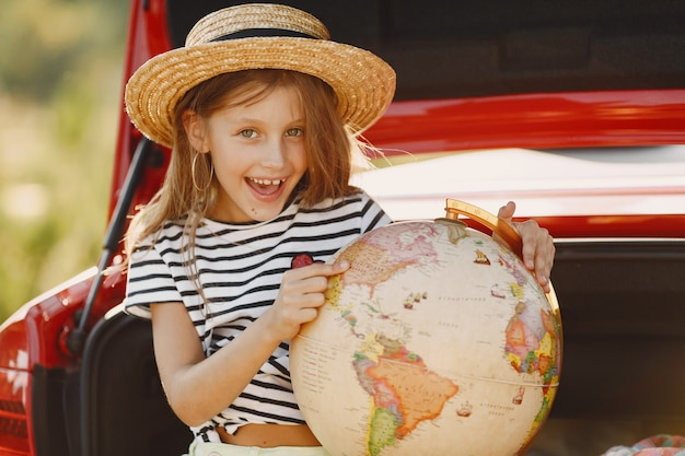 Little girl ready to go on vacations. kid in a red car. girl with globe and hat.