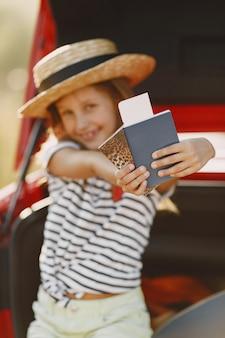 Bambina pronta per andare in vacanza. bambino seduto in una macchina esaminando una mappa. ragazza con passaporto.