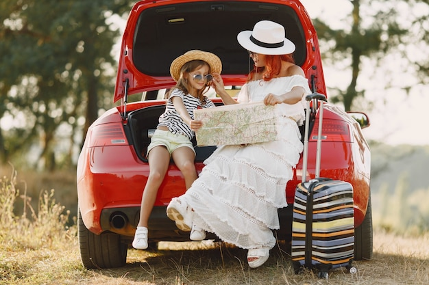 Little girl ready to go on vacations. mother with daughter examining a map. traveling by car with kids.