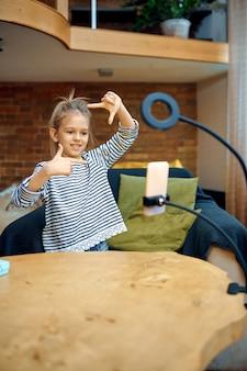 Маленькая девочка записывает видеоблог на камеру телефона, ребенок-блогер