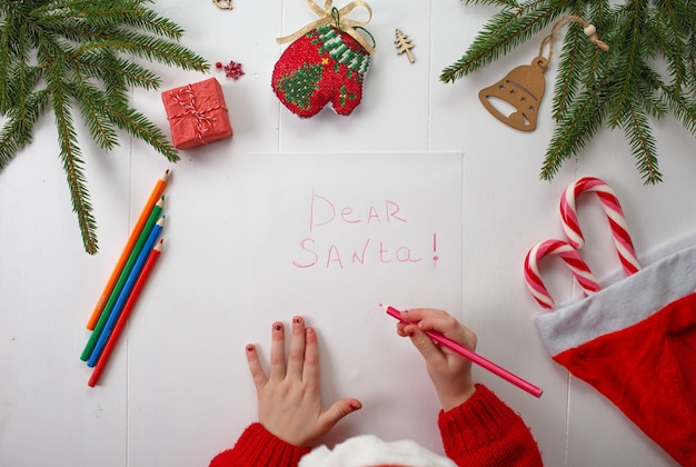 A little girl in a red christmas hat writes a letter to santa claus.