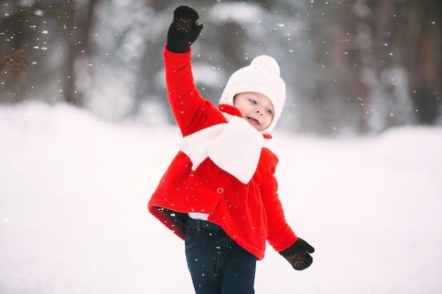 Little girl in red coat with a teddy bear having fun inn winter day