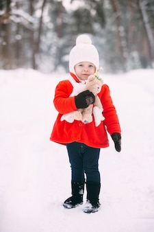 Little girl in red coat with a teddy bear having fun on winter day. girl playing in the snow