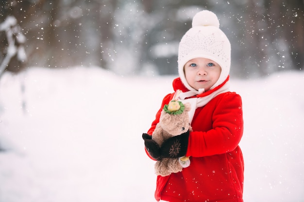 Little girl in red coat with a teddy bear having fun in winter day.