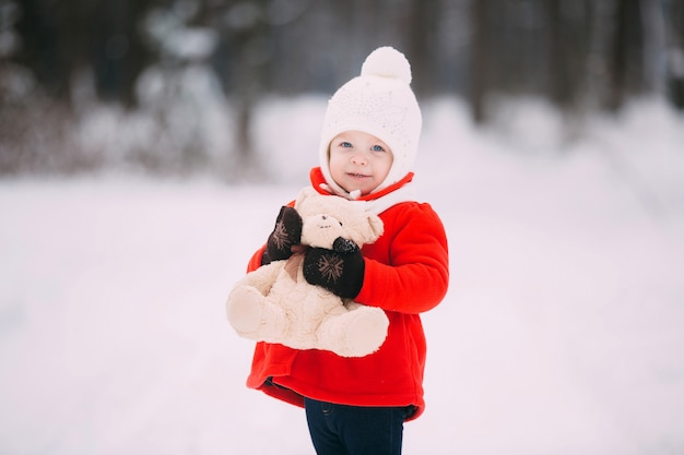 Little girl in red coat with a teddy bear having fun on winter day.