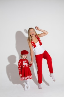 Little girl in red dress and hat poses for the camera with her cheerful mother