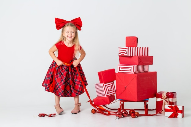 A little girl in a red dress rolls a sled with gifts for the new year. white background, space for text. the concept of christmas