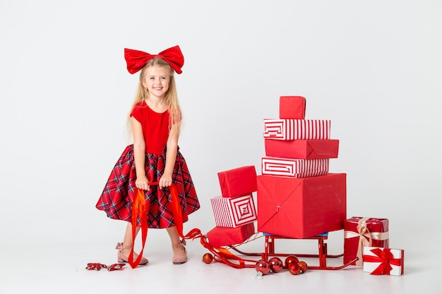 Little girl in a red dress rolls a sled with gifts for the new year. white background, space for text. the concept of christmas