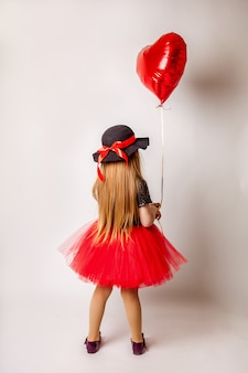 A little girl in a red dress stands with her back