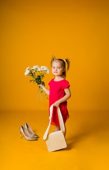 Little girl in a red dress with a beige handbag holds a bouquet of white flowers on a yellow surface with space for text