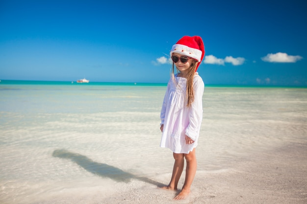 Little girl in red hat santa claus and sunglasses on the beach