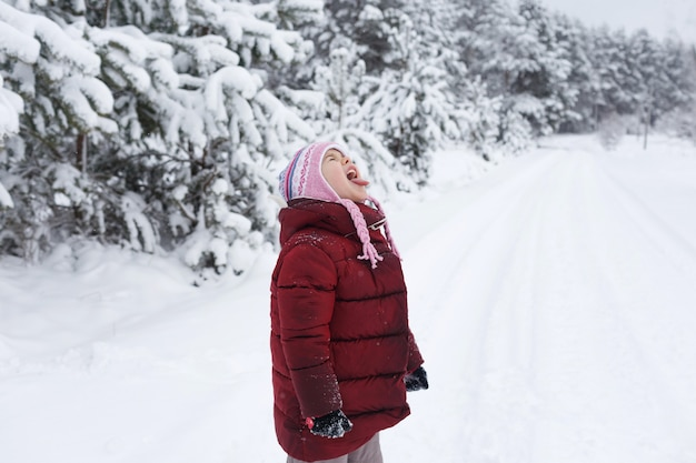A little girl in a red jacket stands in a snow-covered forest catching snowflakes with her tongue.