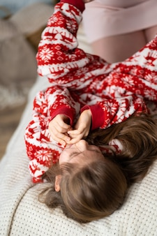 Little girl in red pajamas playing with mom on the bed