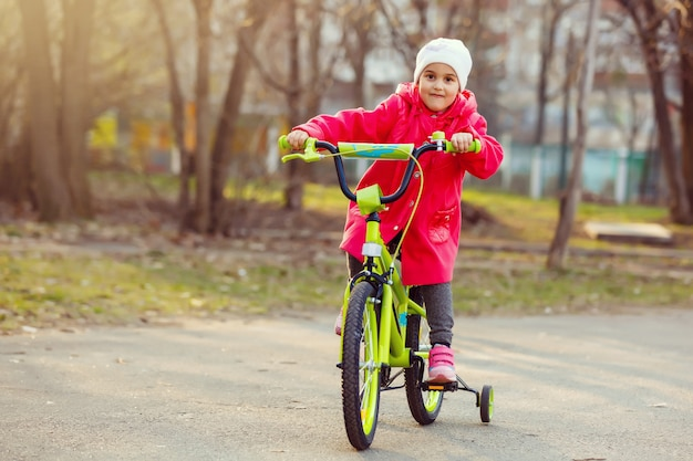 Little girl in red riding a bicycle outdoors