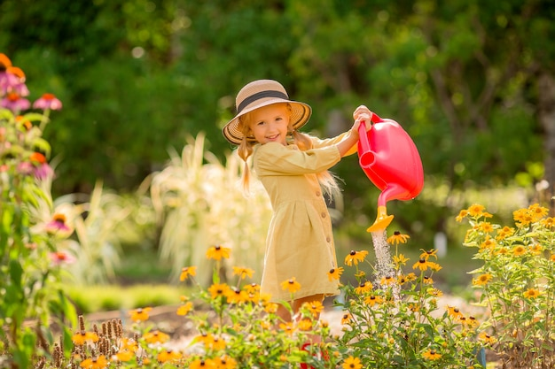 Little girl in red rubber bootswatering flowers in the garden