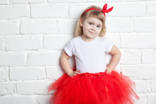 Little girl in a red skirt near a white brick wall