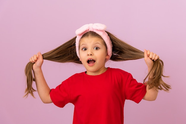 A little girl in a red t-shirt holds her hair in her hands.