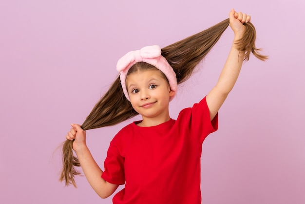A little girl in a red t-shirt pulls her hair in different directions.