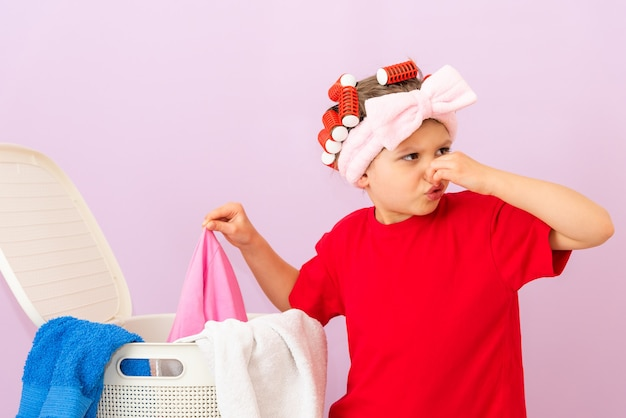 A little girl in a red t-shirt and with curlers on her head really does not like dirty clothes.