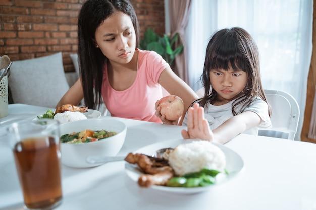 Little girl refuses to eat vegetable rice
