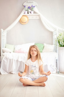 Little girl relax and meditates in yoga pose in bed